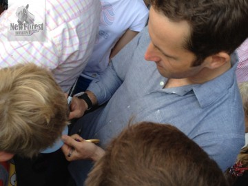 Ben Ainslie signing an autograph, gold medal in hand